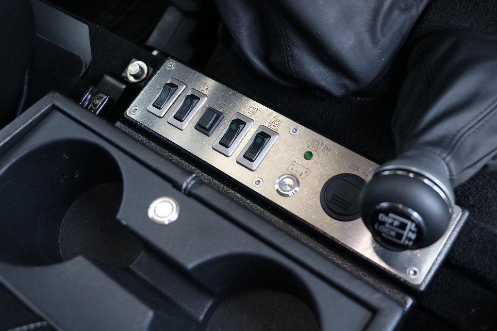 Schalterbelegung von links nach rechts: ABS/TC, Druckluftkompressor, Sofortheiztaste Webasto Airtop, Pumpe Unterflurtank links, dito rechts, Kontrollleuchte für heizbaren Separ-Kraftstofffilter, Notstarttaste Dopelbatteriesystem, Doppel-USB.